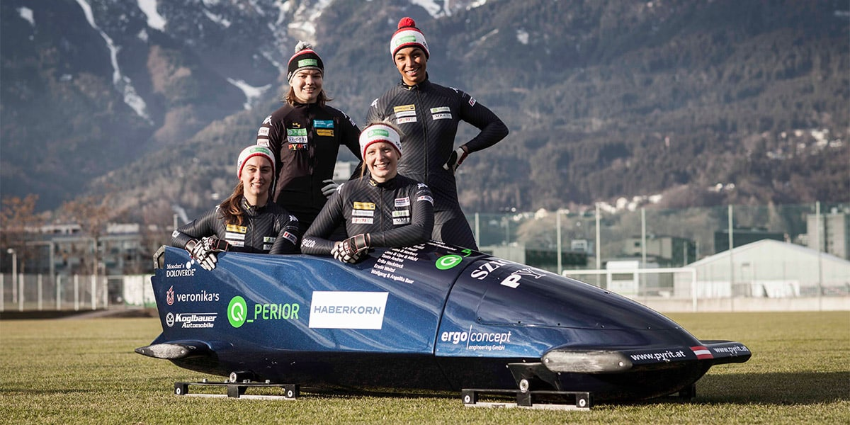 Kati Baierl standing with her bobsled team.
