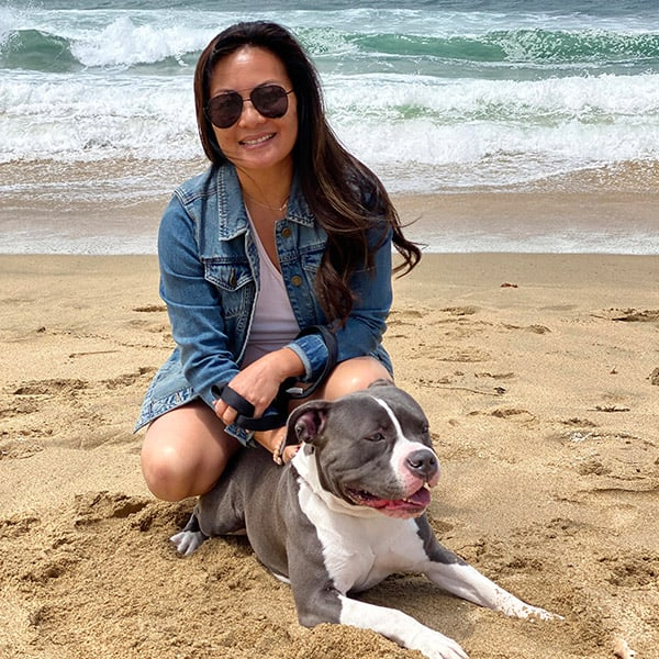 Tracie Noriega posing at the beach with her dog.